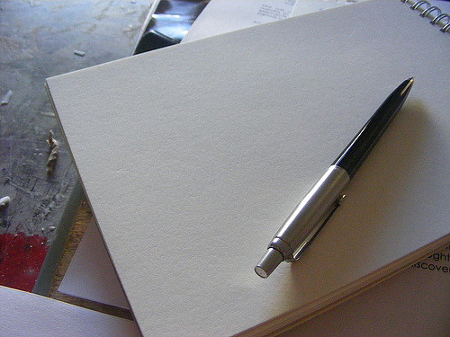 A pen rests atop a sprial-bound pad of blank sketch paper.