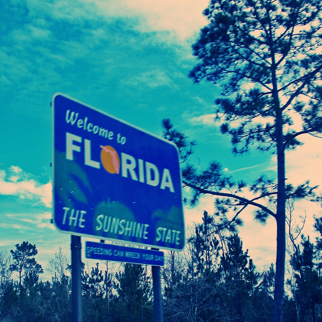 "A road sign set against a backdrop of pine trees and blue skies reads ""welcome to Florida, the sunshine state."""