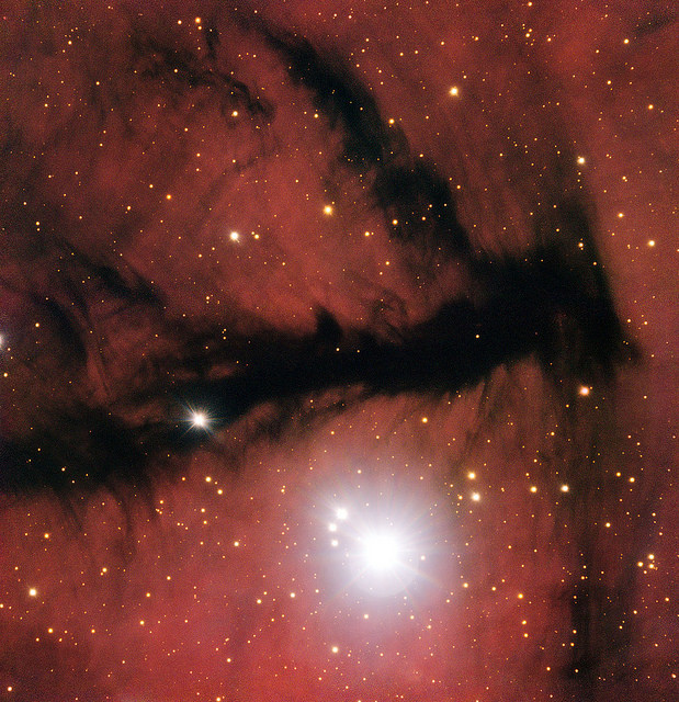 An image from the European Southern Observatory. An image of space. Bright stars can be seen through transparent red atmospheric clouds.