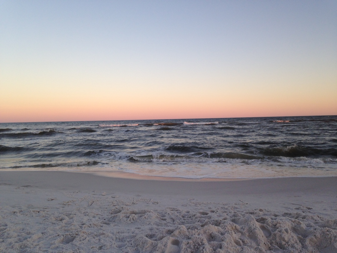 The sky slowly changes colors during sunset over a tranquil beach with small waves and white sand.
