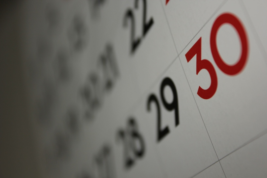 Most of a calendar is blurry in the background, with the focus on the bright red number thirty.
